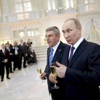 Photo - Russian President Vladimir Putin, right, and International Olympic Committee President Thomas Bach greet IOC members at a welcoming event ahead of the 2014 Winter Olympics at the Rus Hotel, Tuesday, Feb. 4, 2014, in Sochi, Russia. (AP Photo/David Goldman, Pool)