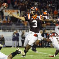 Photo - Virginia Tech quarterback Logan Thomas, center, throws to an open receiver while under pressure from Rutgers defensive end Marvin Booker, bottom right, during the second quarter of an NCAA college football Russell Athletic Bowl game on Friday, Dec. 28, 2012, in Orlando, Fla. (AP Photo/Brian Blanco)