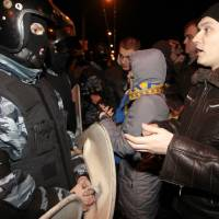 Photo - Pro-European Union activists argue with riot police near a Svyatoshin police station in Kiev, Ukraine, Saturday, Jan. 11, 2014. Kiev has been the scene of massive pro-European protests for more than a month, triggered by Ukrainian President Viktor Yanukovych's decision to ditch a key deal with the European Union in favor of building stronger ties with Russia. (AP Photo/Sergei Chuzavkov)