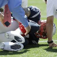 Photo -   New England Patriots tight end Aaron Hernandez holds his right lower leg as he lies on the field in the first quarter of an NFL football game against the Arizona Cardinals, Sunday, Sept. 16, 2012, in Foxborough, Mass. (AP Photo/Elise Amendola)