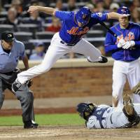 Photo - New York Mets' Daniel Murphy jumps over Milwaukee Brewers catcher Martin Maldonado attempting to score as umpire Dale Scott, left, and batter Travis d'Arnaud, right, look on during the sixth inning of a baseball game Friday, Sept. 27, 2013, in New York. Murphy was tagged out after he didn't touch the plate. (AP Photo/Bill Kostroun)