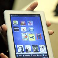 Photo -   FILE - In this Nov. 7, 2011 file photo provided by Barnes & Noble a demonstrator holds the new Barnes & Noble Nook Tablet following a news conference in New York. Tablets are the most-desired electronic device this holiday shopping season, second only to clothing as the gift people are craving most. (AP Photo/Barnes & Noble, Jim Sulley, File)