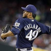 Photo - Milwaukee Brewers' Yovani Gallardo throws a pitch against the Arizona Diamondbacks during the first inning of a baseball game on Thursday, June 19, 2014, in Phoenix. (AP Photo/Ross D. Franklin)