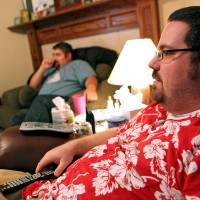 Photo - Alex Gates (right) and guests watch television during a
