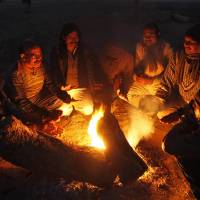 Photo - Indians warm themselves around a bonfire at the Sangam, the confluence of rivers Ganges, Yamuna and the mythical Saraswati in Allahabad, India, Friday, Dec. 28, 2012. North India continues to face extreme weather conditions with dense fog affecting flights and trains and cold wave conditions claiming more than 50 lives, according to local reports. (AP Photo/Rajesh Kumar Singh)