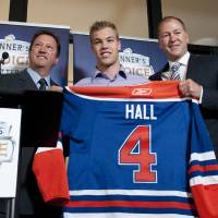 Photo - Edmonton Oilers general manager Steve Tambellini, left, holds up a jersey with draft pick Taylor Hall, center, and Kevin Lowe, the NHL team's president of hockey operations, in Edmonton, Alberta, on Wednesday, Sept. 8, 2010. Lowe, the Oilers' first-ever draft pick and only player to wear the number since Edmonton entered the NHL in 1979, passed his No. 4 to Hall, the centerpiece of a full-scale rebuild in Edmonton and the franchise's first No. 1 overall draft pick. (AP Photo/The Canadian Press, John Ulan) ORG XMIT: JCU102