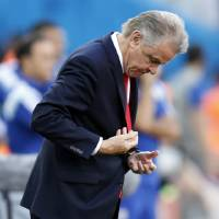 Photo - Switzerland's coach Ottmar Hitzfeld looks down during the World Cup round of 16 soccer match between Argentina and Switzerland at the Itaquerao Stadium in Sao Paulo, Brazil, Tuesday, July 1, 2014. (AP Photo/Frank Augstein)