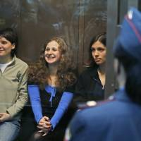 Photo -   FILE - In this Oct. 10, 2012 file photo. feminist punk group Pussy Riot members, from left, Yekaterina Samutsevich, Maria Alekhina, and Nadezhda Tolokonnikova sit in a glass cage at a court room in Moscow. Russia's Prime Minister Dmitry Medvedev said Friday, Nov. 2, 2012 that he detested the Pussy Riot act, but added the women have been in prison long enough and should be released. (AP Photo/Sergey Ponomarev, File)