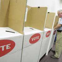 Photo - Norman Neaves, of Oklahoma City, in the voting booth at precinct 416 in Oklahoma City in 2010. In the April 2016, Democrats allowed voters registered independent to cast ballots their party's primary election. The Oklahoman Archives