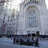 Photo - Police walk with the hearse containing the body of former New York City Mayor Ed Koch as it arrives at Temple Emanu-El for his funeral in New York, Monday, Feb. 4, 2013.   Koch died Friday of congestive heart failure at age 88.  (AP Photo/Seth Wenig)