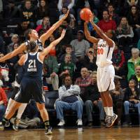 Photo - Virginia guard Faith Randolph (20) shoots a 3-point basket over Notre Dame guard Kayla McBride (21) and forward Natalie Achonwa during the first half of an NCAA college basketball game on Sunday, Jan. 12, 2014, in Charlottesville, Va. (AP Photo/Andrew Shurtleff)
