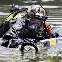 Photo - A Connecticut State Police dive team member searches Pine Lake in Bristol, Conn., the hometown of the former New England Patriots player Aaron Hernandez,  Monday, July 29, 2013. Police divers were in Pine Lake on Monday and other officers could be seen combing the water's edge. Hernandez has pleaded not guilty to murder in the death of Odin Lloyd, a 27-year-old Boston semi-professional football player. (AP Photo/Jessica Hill)