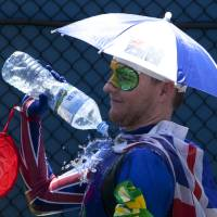 Photo - A spectators pours water over himself to cool down as play was suspended when organizers implemented the Extreme Heat policy during second round matches at the Australian Open tennis championship  in Melbourne, Australia, Thursday, Jan. 16, 2014. (AP Photo/Joshua Baker)