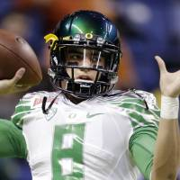Photo - FILE-This Dec. 30, 2013 file photo shows Oregon's Marcus Mariota warms up for the Valero Alamo Bowl NCAA college football game against Texas in San Antonio. All eyes will be on Mariota when the Ducks take the field this season. The junior quarterback could have bolted for the NFL this spring but he decided to stay with the Ducks, who were ranked as high as No. 2 last season before two losses took them out of contention for the national championship. (AP Photo/Eric Gay,File)