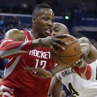 Photo - Houston Rockets center Dwight Howard (12) is fouled by New Orleans Pelicans center Melvin Ely (4) in the first half of an NBA basketball game in New Orleans, Wednesday, April 16, 2014. (AP Photo/Gerald Herbert)