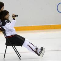 Photo - Sena Suzuki, left, of the Japan women's ice hockey team, pushes teammate Tomoe Yamane on a chair prior their practice session ahead of the 2014 Winter Olympics, Thursday, Feb. 6, 2014, in Sochi, Russia. (AP Photo/Petr David Josek)