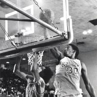 Photo - Northwest's Darryl Kennedy, right, scores two points during his 37-point performance against John Marshall. John Marshall's Tracy Moore, left, scored 24 points in the game. Photo from The Oklahoman Archive