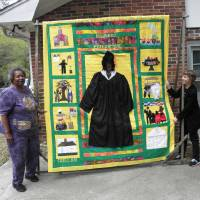 Photo -  Bunny Rodrigues, left, shows the author the quilt honoring Michelle Obama that she spearheaded. Photo courtesy of Victor Block.