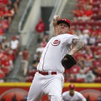 Photo - Cincinnati Reds starting pitcher Mat Latos throws against the Cleveland Indians during the first inning of a baseball game, Wednesday, Aug. 6, 2014, in Cincinnati. (AP Photo/David Kohl)