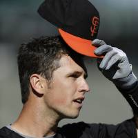 Photo - San Francisco Giants' Buster Posey removes his cap during batting practice before an exhibition spring training baseball game against the Oakland Athletics, Thursday, March 28, 2013, in San Francisco. (AP Photo/Ben Margot)