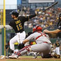 Photo - Pittsburgh Pirates' Ike Davis (15) watches the ball in front of St. Louis Cardinals catcher Yadier Molina after making a base hit, driving in two runs, in the first inning of a baseball game against the St. Louis Cardinals on Friday, May 9, 2014, in Pittsburgh. (AP Photo/Keith Srakocic)