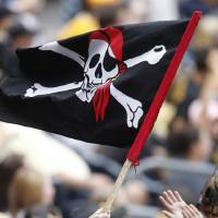 Photo - FILE - In this Sept. 9, 2012, file photo, a young Pittsburgh Pirates fan waves a Jolly Roger flag during the Pirates' baseball game against the Chicago Cubs in Pittsburgh. The Pirates announced on Wednesday, Jan. 8, 2014, the franchise will make the gold