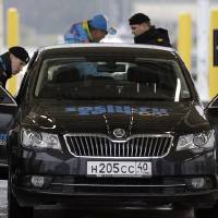 Photo - Russian police officers search a vehicle at an entrance to the Sochi 2014 Olympic Winter Games park, Thursday, Jan. 23, 2014, in Sochi, Russia. The Olympics begin on Feb. 7. (AP Photo/David J. Phillip)