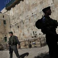 Photo - Israeli border police stand guard while waiting for the arrival of former Foreign Minister Avigdor Lieberman on the site known to Jews as the Tomb of the Patriarchs, and to Muslims as the Ibrahimi Mosque, in the West Bank city of Hebron, Monday, Jan. 14, 2013. (AP Photo/Bernat Armangue)