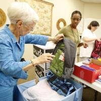 Photo - Mary Frances Dickerson, left, Rev. Valerie Steele, Diana Spencer and Robin Dickerson stuff backpacks at Chapel Hill United Methodist Church in The Village.  Steve Gooch - The Oklahoman