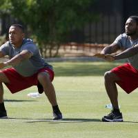 Photo - Arizona Cardinals' Michael Floyd, left, and Antonio Cromartie stretch during the first phase of the voluntary offseason training program at the NFL football team's training facility on Thursday, April 24, 2014, in Tempe, Ariz. (AP Photo/Ross D. Franklin)