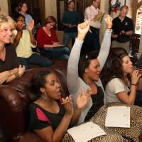 Photo - OU women's basketball coach Sherri Coale, standing, and players, left to right, Jacqueline Jeffcoat, Lyndsey Cloman, Morgan Hook and Whitney Hand react when the Sooners' name is announced during the OU Women's basketball NCAA tournament selection watch party at Coale's residence in Norman Monday, March 12th, 2012. PHOTO BY HUGH SCOTT, FOR THE OKLAHOMAN