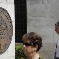 Photo -   Pedestrians pass a plaque portraying a Greek one-drachma coin, which was replaced by the euro in 2002, outside Athens City Hall, on Monday, May 14, 2012. Greek party leaders are to resume power-sharing talks Monday as negotiations to create a government drag into a second week, raising the specter of fresh elections that could threaten the crisis-stricken country's international bailout and its membership of the euro. (AP Photo/Petros Giannakouris)