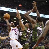 Photo - Cleveland Cavaliers' Kyrie Irving (2) shoots against Toronto Raptors' Landry Fields, left, Kyle Lowry (3), Amir Johnson (15) and Ed Davis (32) during the first half of an NBA basketball game, Saturday, Jan. 26, 2013, in Toronto. (AP Photo/The Canadian Press, Chris Young)