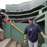 Photo - Cleveland Indians manager Terry Francona walks past photographers as he heads to the bench of the visitor's dugout before a baseball game against the Boston Red Sox at Fenway Park in Boston, Thursday, May 23, 2013. Francona was Red Sox manager for the 2004 and 2007 World Series Championship seasons. (AP Photo/Charles Krupa)