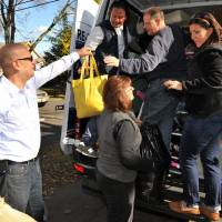 Photo -   David Pasqualino, in truck, and his wife Elena load donations in Emerson, N.J., for relief of Sandy victims in Toms River, N.J. on Sunday, Nov. 4, 2012. Almost a week after Sandy slammed into the New Jersey coastline in an assault that killed more than 100 people in 10 states, nearly 1 million homes and businesses were still without power in New Jersey, and about 650,000 in New York City, its northern suburbs and Long Island. (AP Photo/The Record (Bergen County NJ),Chris Monroe)