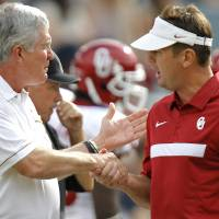 Photo - Oklahoma coach Bob Stoops and Mack Brown shake hands before the start of the Red River Rivalry college football game between the University of Oklahoma Sooners (OU) and the University of Texas Longhorns (UT) at the Cotton Bowl in Dallas, Saturday, Oct. 8, 2011. Photo by Chris Landsberger, The Oklahoman  ORG XMIT: KOD