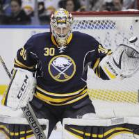 Photo - Buffalo Sabres goaltender Ryan Miller reaches out with his glove to stop the puck during the second period of an NHL hockey game against the Carolina Hurricanes in Buffalo, N.Y., Tuesday, Feb. 25, 2014. Buffalo won 3-2. (AP Photo/Gary Wiepert)