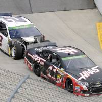 Photo - Brad Keselowski (2) bumps Kurt Busch (41) as they enter Turn 1 during a NASCAR Sprint Cup auto race at Martinsville, Speedway, Sunday, March 30, 2014, in Martinsville, Va. The two drivers were involved in a pit road accident earlier in the race. (AP Photo/Mike McCarn)
