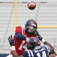 Photo - Mississippi quarterback Bo Wallace, top, throws over the defense of linebacker Serderius Bryant (14) during an NCAA college football spring scrimmage on Saturday, April 5, 2014, in Oxford, Miss. (AP Photo/Rogelio V. Solis)