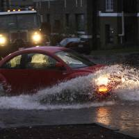 Photo -   Cars and trucks navigate through standing water, Monday, Nov. 19, 2012, at an intersection in Tacoma, Wash. Wet and windy weather with mountain snow will continue this week in Washington, forecasters said. (AP Photo/Ted S. Warren)