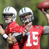 Photo - FILE - In this May 31, 2012, file photo, New York Jets quarterbacks Mark Sanchez, left, and Tim Tebow workout during NFL football practice in Florham Park, N.J. Likely done in New York after one frustrating season and Jacksonville already saying no to a happy homecoming, what's next for Tebow, one of the league's most popular and polarizing players? A backup role on another NFL team? A position change? The Canadian Football League? Well, even Tebow isn't sure.(AP Photo/Julio Cortez, File)