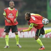 Photo - Brazil's Neymar, right, and Dani Alves, practice during a training session of the Brazilian national soccer team at the Granja Comary training center in Teresopolis, Brazil, Saturday, June 21, 2014. Brazil plays in group A of the 2014 soccer World Cup. (AP Photo/Andre Penner)