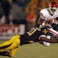 Photo - Oklahoma's Ryan Broyles (85) tries to leap past Missouri's Jarrell Harrison (11) during the first half of the college football game between the University of Oklahoma Sooners (OU) and the University of Missouri Tigers (MU) on Saturday, Oct. 23, 2010, in Columbia, Mo.  Photo by Chris Landsberger, The Oklahoman