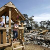 Photo - CHEYANN FORD / SARA FORD / FIRES / DAMAGE / AFTERMATH / KIDS / CHILDREN: Sisters Sara, 3, and Cheyann (cq) Ford, 5, look out from a wooden swing set on the property next to their grandmother's home at 1004 Pacific Tuesday morning. The girls were playing on the set that escaped flames in last Thursday's wildfires. The home on the lot with the playset  was destroyed. The girls' grandmother's house was slightly damaged when the siding on the south side of the home melted. Assessment teams from FEMA and Oklahoma Emergency Management toured neighborhoods devastated in last Thursday's wildfires.  They toured several neighborhoods on Tuesday,   April 14, 2009.  Photo by JIM BECKEL, THE OKLAHOMAN ORG XMIT: KOD