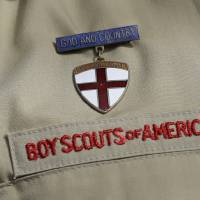 Photo - This photo taken  Monday, Feb. 4, 2013, shows a close up detail of a Boy Scout uniform worn by Brad Hankins, a campaign director for Scouts for Equality, as he responds questions during a news conference in front of the Boy Scouts of America headquarters in Irving, Texas. The Boy Scouts of America's policy excluding gay members and leaders could be up for a vote as soon as Wednesday, when the organization's national executive board meets behind closed doors under intense pressure from several sides. (AP Photo/Tony Gutierrez)