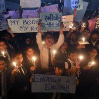 Photo - Indian students and teachers hold candles and placards as they take part in a candle march in Ahmadabad, India, Saturday, Dec. 22, 2012. Police in India's capital used tear gas and water cannons Saturday to push back thousands of people who tried to march to the presidential mansion to protest the recent gang rape and brutal beating of a 23-year-old student on a moving bus. Placard in the center reads as,