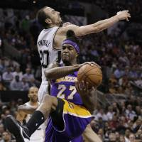 Photo - Los Angeles' Jordan Hill (27) pulls down a rebound next to San Antonio Spurs' Manu Ginobili (20), of Argentina, during the first half of an NBA basketball game, Wednesday, April 16, 2014, in San Antonio. (AP Photo/Eric Gay)