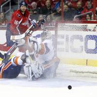 Photo - New York Islanders goalie Evgeni Nabokov (20), from Russia, watches the shot by Washington Capitals right wing Eric Fehr (16) bounce away, in the first period of an NHL hockey game, Tuesday, Feb. 4, 2014, in Washington. (AP Photo/Alex Brandon)
