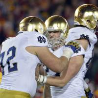 Photo - Notre Dame kicker Kyle Brindza, center, celebrates with offensive tackle Nick Martin after kicking a field goal during the second half of an NCAA college football game against Southern California, Saturday, Nov. 24, 2012, in Los Angeles. Notre Dame won 22-13. (AP Photo/Mark J. Terrill) ORG XMIT: LAC114