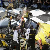 Photo - Marcos Ambrose is doused by his race team as he climbs from his car to celebrate in Victory Lane after winning a NASCAR Nationwide Series auto race at Watkins Glen International, Saturday, Aug. 9, 2014, in Watkins Glen N.Y. (AP Photo/Mel Evans)